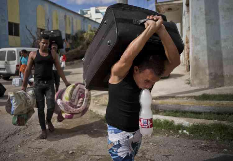 Des habitants de la Havane récupèrent leurs biens avant de rejoindre un centre d'hébergement de la capitale, lundi.
