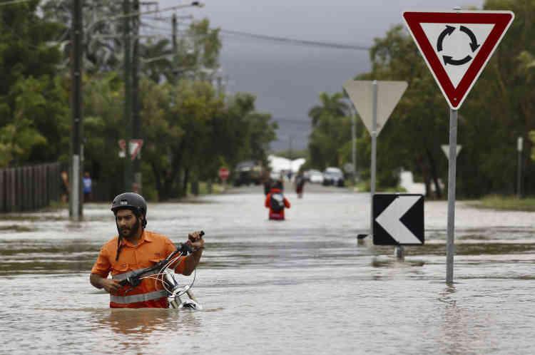 Un habitant pousse son vélo dans les rues inondées d'Hermit Park, dans la banlieue de Townsville. Plus de 1 100 personnes ont été évacuées de leur maison dans la nuit de dimanche à lundi.