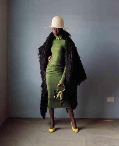 Manteau en laine, Vivienne Westwood Archive. Robe en jersey ornée de cristaux, Alexandre Vauthier. Sac en veau velours et soie, Balenciaga. Escarpins en cuir, Acne Studios. Chapeau en feutre, House of Flora.