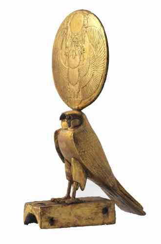 «Cette figure de faucon solaire a été découverte dans le coin sud-est de l'antichambre, derrière un char. Une image du dieu scarabée Khépri décore les deux faces du disque qui coiffe la tête du faucon. De larges ailes d'oiseau se déploient de part et d'autre du corps d'insecte du dieu. Au-dessus de la tête du scarabée, le disque solaire est flanqué d'une paire d'uræi qui portent des ânkhs suspendus à leurs corps reptiliens. Chaque uræus porte la double couronne de Haute et de Basse-Egypte. Trois ânkhs supplémentaires pendent du disque solaire. Sous le scarabée, on voit trois traits indiquant le pluriel et un panier neb.»