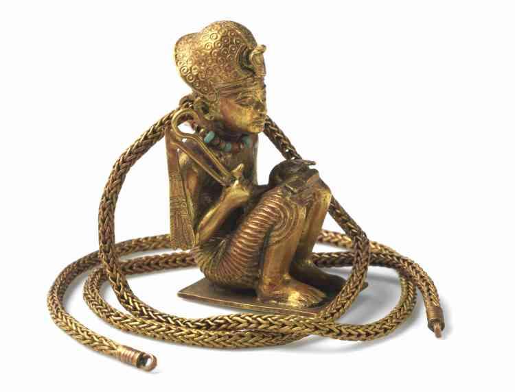 « L'archéologue Howard Carter a découvert une mèche de cheveux enveloppée dans du lin et ce pendentif en or dans un emboîtement de cercueils anthropomorphes dédicacés à Toutankhamon. Une inscription sur le lin nous apprend que ce sont des cheveux de la reine Tiyi, la grand-mère de Toutankhamon. Carter et d'autres après lui croyaient que la figurine représentait le grand-père du roi, AmenhotepIII. Cependant, les marques sur les oreilles de la figure indiquent qu'elles sont percées. Par conséquent, ce doit être Toutankhamon lui-même. AmenhotepIII n'apparaît jamais les oreilles percées.»