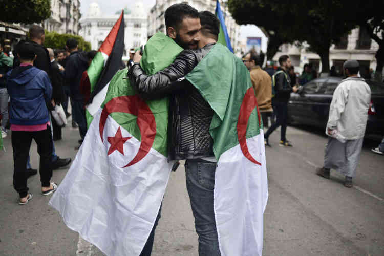 Un moment de tendresse, à Alger, entre deux manifestants qui ont revêtu le drapeau national.