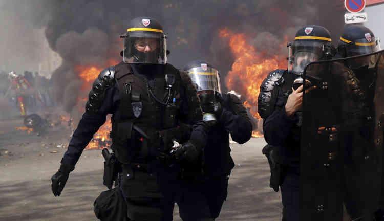 Des policiers à proximité de véhicules incendiés lors de la manifestation des« gilets jaunes», le 20 avril.