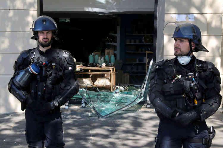 Des policiers dos à la devanture d'un magasin détruite lors de la manifestation des«gilets jaunes» à Paris, le 20 avril.