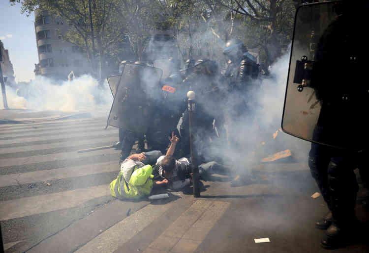 Des membres des forces de l'ordre chargent des manifestants, à Paris, le 20 avril.