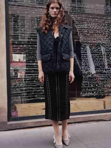 Veste matelassée en nylon, Barbour. Cardigan en laine et cachemire, Miu Miu. Robe à lacets en maille, Dolce & Gabbana. Collants en nylon, Wolford. Boucle d'oreille en argent et strass, Balenciaga. Escarpins imprimés pied-de-poule, Dior.