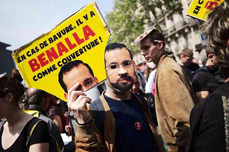 Des manifestants portent des masques du visage d'Alexandre Benalla lors de la manifestation du 1er-Mai à Paris.