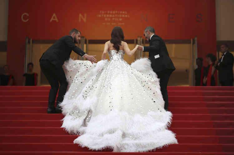 La chanteuse Jessica Jung a besoin d'aide pour monter les marches dans sa volumineuse robe.