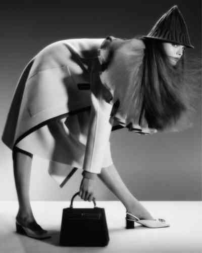 Manteau en double face cachemire et ganse de cuir, jupe en laineet sac Kelly 2sellier 25 en veau barénia, HERMÈS. Blouse en crêpe de soie avec collerette plissée, Stella McCartney. Chapeau encachemire tricoté, Dior.Chaussures en cuir et métal doré, Balenciaga.