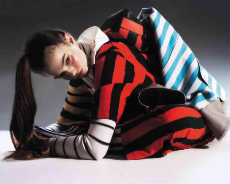 Manteau en toile enduite à rayures porté autour de la taille, Sunnei. Sous-pull àcol roulé en polyester, Calvin Klein205W39NYc. Robe polo en coton rayé etsac puzzle en cuir rayé, Loewe.Collantsrayés en Nylon, Emilio Cavallini.