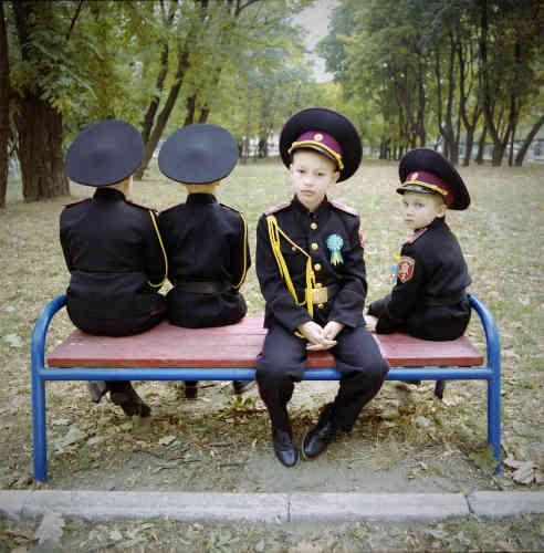 «Tandis que les garçons arborent différents types d'uniformes : type camouflage au quotidien et noir lors des cérémonies ou en service – comme ces jeunes cadets lors d'une pause. Le rôle « guerrier » des garçons et celui « décoratif » des filles est inscrit dans la tradition d'éducation des anciens pensionnats militaires et se perpétue, assignant des rôles et des valeurs traditionnelles dès le plus jeune âge à cette future élite.»