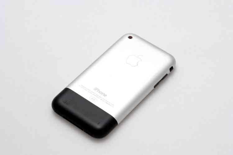 Le tout premier iPhone, annoncé en 2007, vu de dos. Son dessin ne comporte qu'un bouton en façade : on le pilote au doigt grâce à son écran tactile multipoint et c'est une idée qui tranche à cette époque. Ce smartphone clef marque l'avènement des interfaces tactiles, qui réduiront la marge de liberté des designers comme peau de chagrin. Après cette sortie, les smartphones se ressembleront chaque année un peu plus.