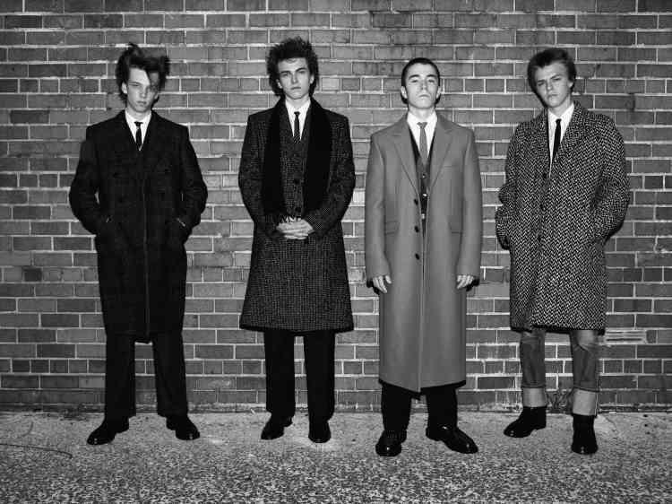 De gauche à droite, manteau en laine prince-de-galles, chemise et cravate en coton, pantalon en laine et derbys en cuir.Manteau en tweed, chemise et cravate en coton, pantalon en laine, écharpe en laine et derbys en cuir.Manteau en laine camel, cardigan en laine mohair, chemise et cravate en coton, pantalon en laine et creepers en cuir.Manteau en laine pied-de-poule, chemise et cravate en coton, jeans en coton et bottines en cuir, Celine parHedi Slimane.