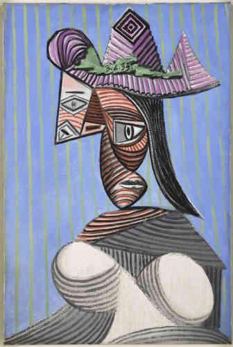 «La photographe Dora Maar est devenue en 1935 la maîtresse attitrée de Picasso. La jeune femme va vivre deux guerres auprès du peintre de Malaga: la guerre civile espagnole et la Seconde Guerre mondiale. Buste de femme au chapeau rayé offre une tête démente, hallucinée coiffée d'un chapeau mauve et rayé qui se détache sur un mur tapissé d'un papier peint à rayures bleues et jaunes. Celle qui avait incarné «La Femme qui pleure» révèle un visage difforme et contorsionné qui progressivement deviendra le visage collectif de la guerre ».