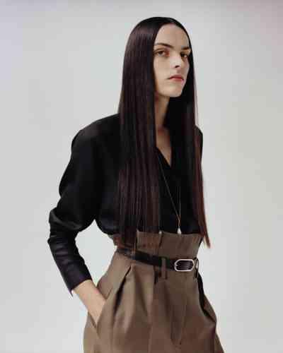 Chemise en satin de soie, Berluti. Pantalon taille haute en laine et ceinture en cuir et boucle argentée, Acne Studios. Collier chaîne et perle, Celine par Hedi Slimane.