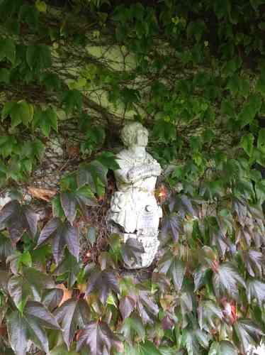 Enigmatique, l'élément sculpté est adossé à un mur recouvert de vigne vierge.