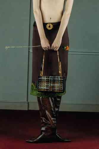 Collier en laiton et cuir porté en ceinture, LOEWE.Sac Lola en tweed et agneau, BURBERRY.Jupe en satin et dentelle, VERSACE.Bottes Maxima en cuir façon serpent, JIMMY CHOO.