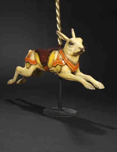 «Ce lièvre provient d'un manège pour petits. Il a été réalisé et au début du XXesiècle par un artiste de l'école allemande du nom de Joseph Hübner. Il est typique du style de cette école, de par son harnachement excessif et le réalisme du sujet.»