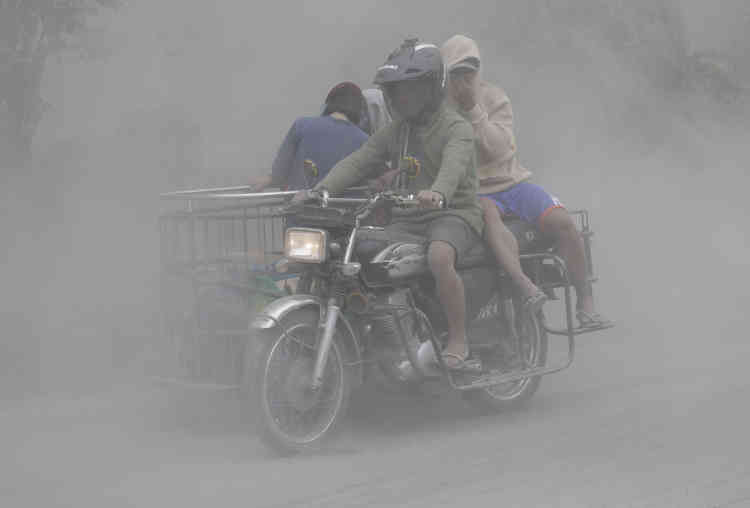 13 janvier. Le volcan Taal continue ses éruptions près de Lemery, dans la province de Batangas (sud des Philippines). Une famille se déplace à moto dans un nuage de cendre pour aller vers un endroit plus sûr.