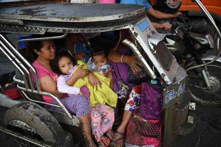 13janvier. Des habitants de Tanauan évacuent la ville à bord d'un tricycle couvert de cendre.