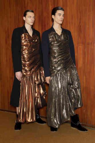 Chez Loewe, Jonathan Anderson alterne les silhouettes sobres et celles dont la fantaisie emprunte au vestiaire féminin. Comme ces premiers looks, où un tablier garni de vagues de tissu lamé or posé sur un costume donne l'impression que le mannequin porte une robe de bal.