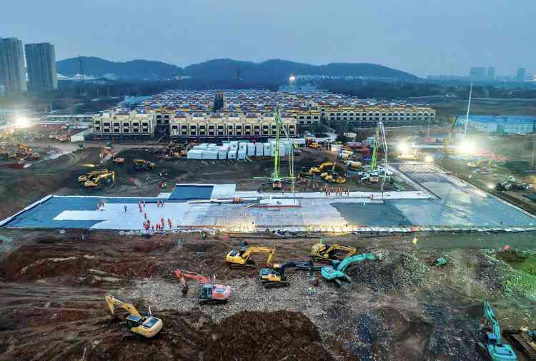 Premier coulage du béton dans la soirée du 27janvier.Situé à une vingtaine de kilomètres au sud-ouest de Wuhan, le nouvel hôpital se dresse au bord d'une route à deux fois deux voies dont un sens de circulation a été entièrement coupé pour permettre le passage de dizaines de camions de livraison et d'engins de terrassement.