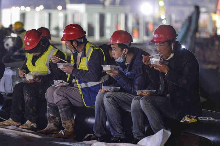 Pause repas pour quelques-uns des sept mille ouvriers qui se sont relayés nuit et jour pour tenir le délai de construction (dix jours).