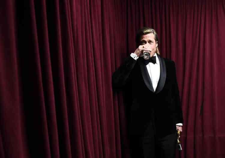 En coulisses, Brad Pitt, sa statuette à la main, célèbre son entrée dans l'histoire des Oscars d'un verre… d'eau.