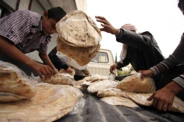 Men transport bread from a pick-up truck in Kafruma, an area of the province of Idlib, during the Muslim holiday of Eid al-Adha October 26, 2012. Picture taken October 26, 2012. 