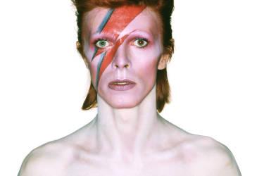"""Photographie de David Bowie pour la pochette de l'album """"Aladdin Sane"""" (1973). Conception par Brian Duffy et Celia Philo, maquillage par Pierre La Roche."""