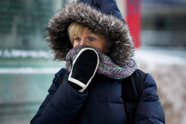 A woman shields her face as she departs from Union Station with wind chills nearing minus 30 Fahrenheit on Tuesday, Jan. 7, 2014, in downtown Chicago.  Dangerously cold polar air snapped decades-old records as it spread Tuesday from the Midwest to southern and eastern parts of the U.S. and eastern Canada, making it hazardous to venture outside and keeping many schools and businesses closed. (AP Photo/Andrew A. Nelles)