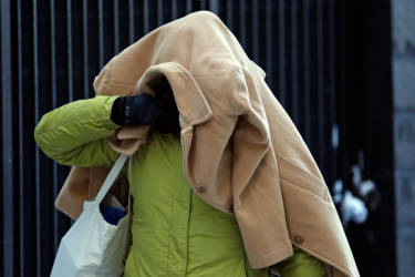 A woman covers her head with a jacket as she walks in frigid cold temperatures though downtown Chicago, Illinois, January 6, 2014. A blast of Arctic air gripped the mid-section of the United States on Monday, bringing the coldest temperatures in two decades. Meteorologists said temperatures were dangerously cold and life-threatening in some places, with 0 degrees Fahrenheit (minus 18 Celsius) recorded in Chicago, St. Louis and Indianapolis. The chill was set to bear down on eastern and southern states as the day wore on. REUTERS/Jim Young (UNITED STATES - Tags: ENVIRONMENT SOCIETY)