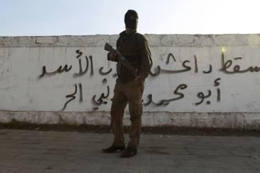 Un combattant de l'armée syrienne libre pose devant un graffiti condamnant l'Etat islamique en Irak et au Levant, à Alep, le 7 janvier.