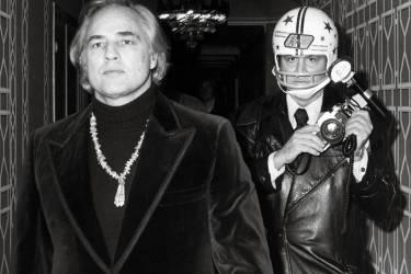 Le 26 novembre 1974, Marlon Brando assiste à un gala de  charité à New York, suivi par l'un des pionniers des paparazzis, Ron Galella, qui n'approche plus l'acteur que casqué, après s'être fait casser la mâchoire. Une photo réalisée par Paul Schmulbach.Photo: Ron Galella/WireImage