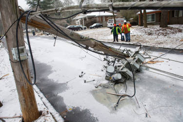 A crew asses the situation in front of a downed transformer smashed in the road during a winter storm on Wednesday, Feb. 12, 2014, in Doraville, Ga. About 175,000 customers were without power Wednesday afternoon, power companies reported.  (AP Photo/John Amis)