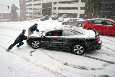 Pedestrians help a motorist after her car ends up facing the wrong way while trying to make it up the hill on Hawthorne Road at Wake Forest Baptist Medical Center in Winston-Salem, N.C. as snow falls Wednesday, Feb. 12, 2014. (AP Photo/Winston-Salem Journal, Lauren Carroll)
