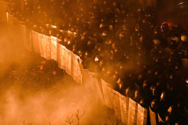 Riot police face anti-government protesters during clashes during the storming of Independence Square in Kiev on February 18, 2014. Flames engulfed the main anti-government protest camp on Kiev's Independence Square as riot police tried to force demonstrators out following the bloodiest clashes in three months of protests. The iconic square turned into a war zone as riot police moved slowly through opposition barricades from several directions, hurling stun grenades and using water cannon to clear protestors.    AFP PHOTO/SERGEI SUPINSKY
