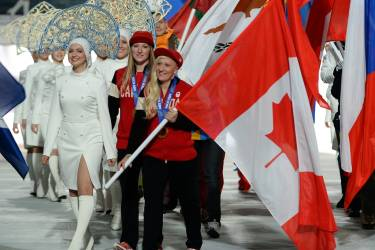 Canada's flag bearer, bobsledders Kaillie Humphries and Heather Moyse take part in the Closing Ceremony of the Sochi Winter Olympics at the Fisht Olympic Stadium on February 23, 2014. AFP PHOTO / PETER PARKS