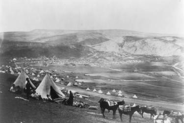 Military encampment showing conical tents, people, and horses, with mountains in the background