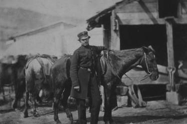 Captain Bathurst, full-length portrait, dressed in uniform, standing next to a horse with other horses and buildings in the background.