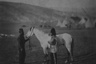 """Colonel George Clarke, full-length portrait, wearing uniform, standing beside his horse, Sultan, facing left; horse's reins are held by a man who is possibly a servant; horse's rump is branded """"2D"""" for 2nd Dragoons; encampment of tents in background."""