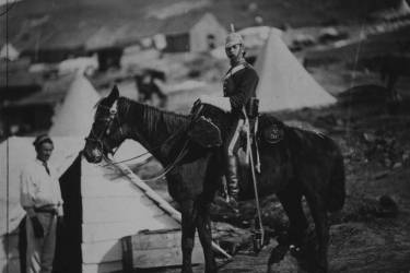 """aptain Bernard(?), full-length portrait, dressed in uniform, seated on a horse with """"V DG"""" on bags, facing left; another man, possibly a servant, stands at the head of the horse, tent and huts in the background."""