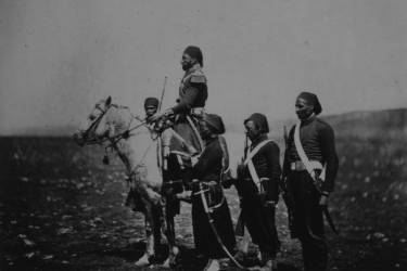 Ismail Pacha (General Kmety), full-length portrait, seated on horse, facing left, with three attendants in the foreground and one in the background.