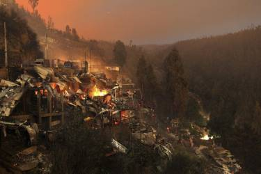 Destroyed houses are seen at the location where a forest fire burned several neighbourhoods in the hills in Valparaiso city, northwest of Santiago, April 13, 2014. At least 12 people were killed and 2,000 houses destroyed over the weekend by a fire that devastated parts of the Chilean port city of Valparaiso, as authorities evacuated thousands and sent in aircraft to battle the blaze. REUTERS/Cristobal Saavedra (CHILE - Tags: SOCIETY ENVIRONMENT DISASTER)
