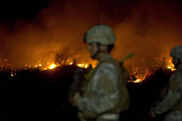 Chilean soldiers patrol next to a fire after some focuses reactivated, in Valparaiso, Chile, on April 13, 2014. More than 10,000 people were evacuated as an army of firefighters battled a killer blaze that --on the eve-- tore through parts of Chile's historic port of Valparaiso and left at least 11 people dead. The fire, which started in woodland Saturday, gutted 500 homes as flames advanced on the city of 270,000, famed for its UNESCO-listed center with cobblestone streets and brightly painted wooden homes. AFP PHOTO/MARTIN BERNETTI
