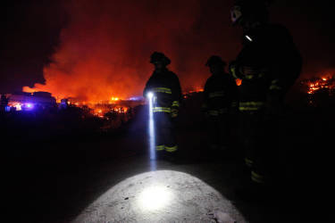 A firefighter shines a flashlight as he stands with others near burning homes as a forest fire rages towards urban areas in the city of Valparaiso, Chile, Sunday April 13, 2014. Authorities say the first fire has destroyed at least 150 homes and is forcing evacuations.( AP Photo/ Luis Hidalgo)