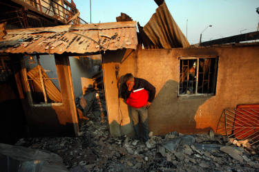 CORRECTS TO LOWER DEATH TOLL TO 11 FROM 16 AFTER POLICE SAY ONE FAMILY HAD BEEN COUNTED TWICE - A man cries next to the remains of his house after a forest fire destroyed it in Valparaiso, Sunday, April 13, 2014. A raging fire leaped from hilltop to hilltop in this port city, killing at least 11 people and destroying more than 500 homes. More than 10,000 people were evacuated. (AP Photo/Luis Hidalgo)