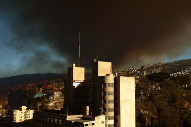 A cloud of smoke from burning houses rises over Valparaiso, 110 km west of Santiago, Chile, on April 12, 2014. Authorities decreed a red alert for the area after the fire consumed more than 100 houses.   AFP PHOTO / FELIPE GAMBOA