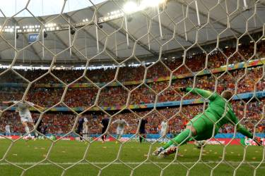 Spain's midfielder Xabi Alonso (L) scores a penalty during a Group B football match between Spain and the Netherlands at the Fonte Nova Arena in Salvador during the 2014 FIFA World Cup on June 13, 2014.  AFP PHOTO / DAMIEN MEYER