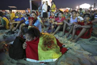 Wrapped in a Spanish national flag, a soccer fan watches the live broadcast of the World Cup match between Spain and the Netherlands inside the FIFA Fan Fest area on Copacabana beach in Rio de Janeiro, Brazil, Friday, June 13, 2014. The Netherlands thrashed Spain 5-1 Friday. It was a humiliating defeat for the defending World Cup champions. (AP Photo/Leo Correa)